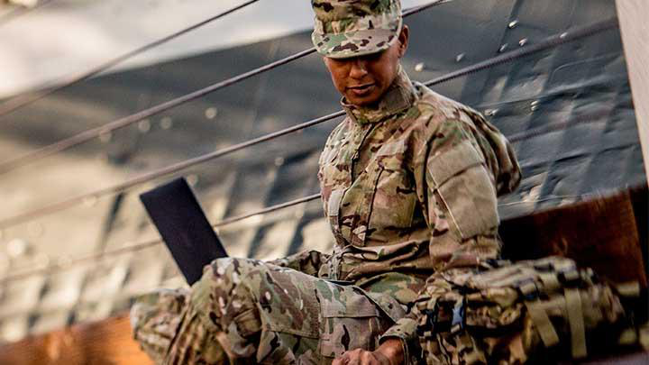 woman in the military studying on laptop