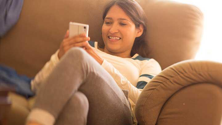 woman on couch with phone