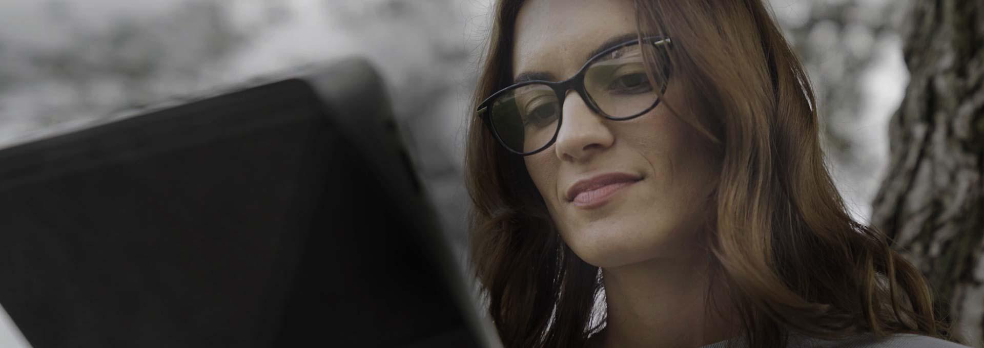 woman wearing glasses viewing a tablet
